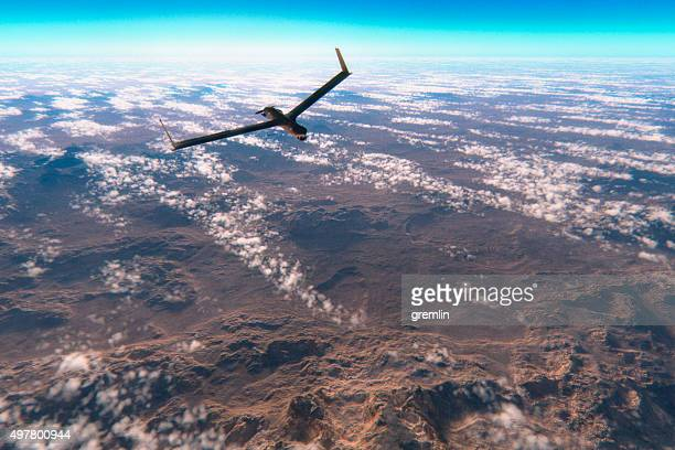 military surveillance drone flying over rocky deserts - military drones stock photos and pictures