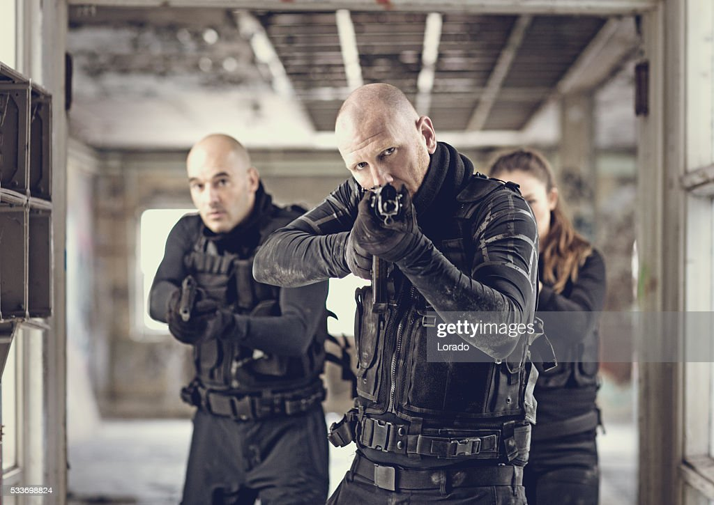 Militare swat i dipendenti in magazzino abbandonato durante il funzionamento : Foto stock