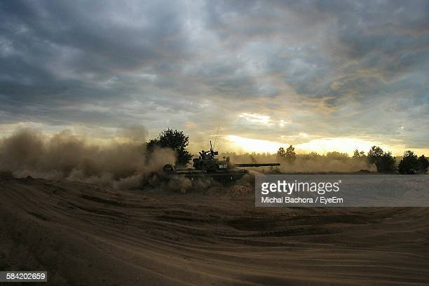 military tank on field against sky during sunset - armored tank stock photos and pictures