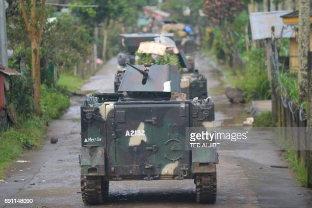 Military tanks maneouver through a village street as they advance towards a position of Islamist militants in Marawi on the southern island of...