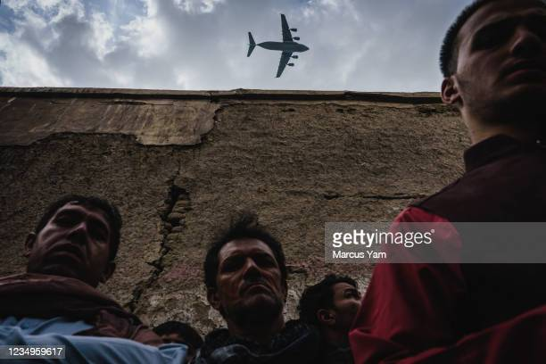 Military transport plane flies over as Relatives and neighbors of the Ahmadi family gathered around the incinerated husk of a vehicle targeted and...