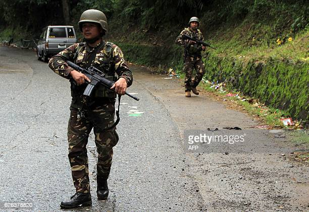 Military troops scour the site of a roadside blast in the village of Matampay in Marawi City Southern Mindanao on November 29 2016 Seven military...