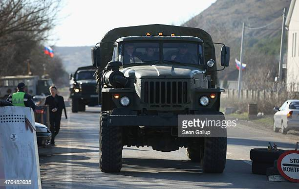 Military trucks with Russian licence plates drive through a checkpoint manned by pro-Russian militants on the main road between Sevastopol and...