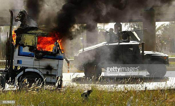 S military vehichle drives past a burning truck that was part of a US military convoy that came under attack April 10 2004 in Baghdad Iraq Much of...