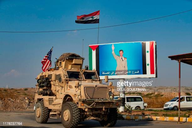 Military vehicle drives near a checkpoint controlled by the Syrian government forces in Syria's northeastern city of Qamishli on October 26, 2019