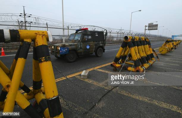 A military vehicle drives past barricades at a military checkpoint leading to the border truce village of Panmunjom in Paju on January 17 2018...