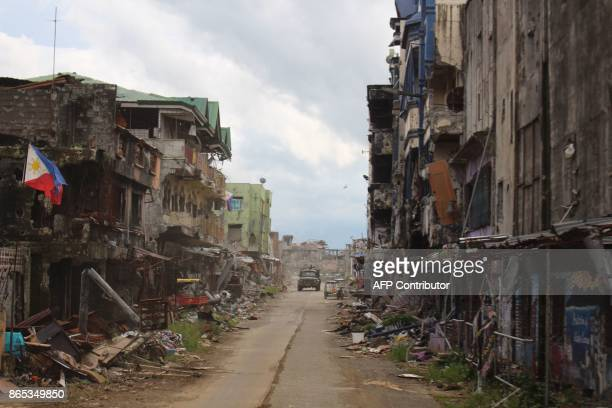 A military vehicle drives past destroyed buildings in what was the main combat area of Marawi on the southern island of Mindanao on October 23 2017 A...