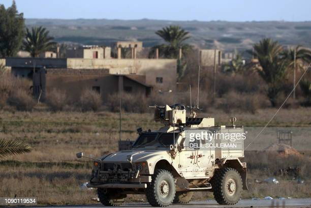A US military vehicle drives through the Syrian village of Baghuz in the countryside of the eastern Deir Ezzor province on January 26 2019 The Syrian...