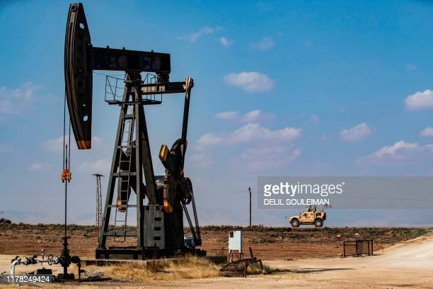 Military vehicle, part of a convoy arriving from northern Iraq, drives past an oil pump jack in the countryside of Syria's northeastern city of...