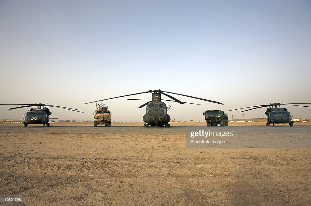U.S. military vehicles and aircraft lined up on the taxiway at Camp  Speicher, Iraq. : Stock Photo