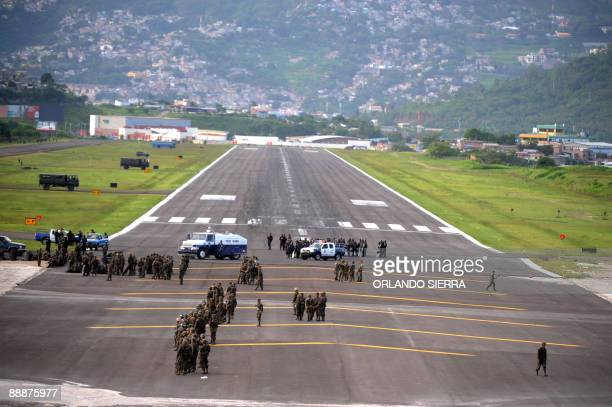 Military vehicles and soldiers block the runway to prevent the landing of the Venezuelan airplane carrying ousted Honduran President Manuel Zelaya at...