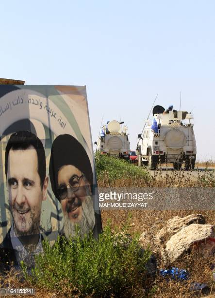 Military vehicles belonging to the United Nations Interim Forces in Lebanon drive past posters of the Lebanese Shiiite Hezbollah movement leader...