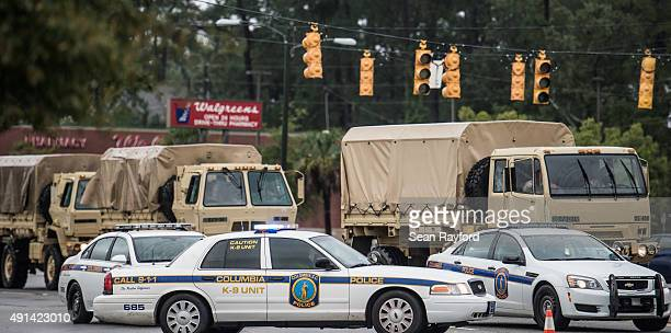 Military vehicles make their way through a police roadblock on Garners Ferry Road following flooding in the area October 5, 2015 in Columbia, South...
