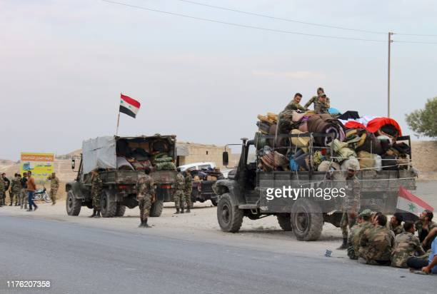 Military vehicles transporting Syrian regime troops and rolled up mattresses are stationed on the outskirts of the northern Syrian border town of...