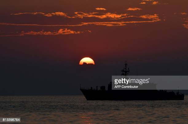A military vessel sails at sunset off Trieste northern Italy on July 12 2017 / AFP PHOTO / TIZIANA FABI