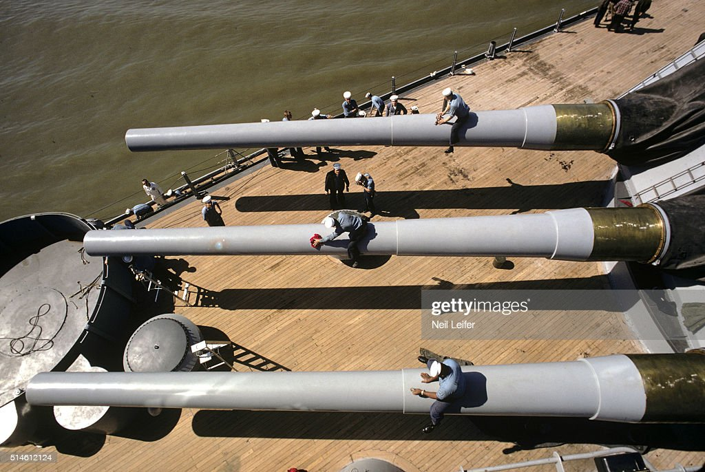 View of crewmembers cleaning the gun barrels of the USS New Jersey