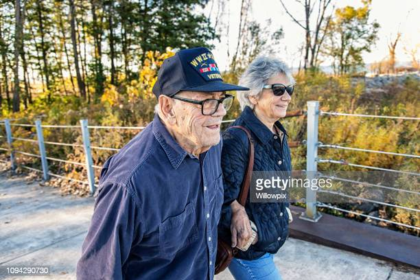 wwii usa military war veteran father and daughter walking - armistice day stock photos and pictures