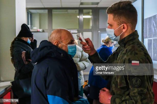 Military wears a protective face mask and gloves as he sreams the temperature of an elderly man before being given the Pfizer/BioNTech COVID-19 jab...