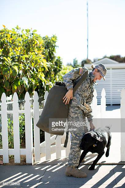 military woman greeting her dog at picket fence - mammal stock pictures, royalty-free photos & images