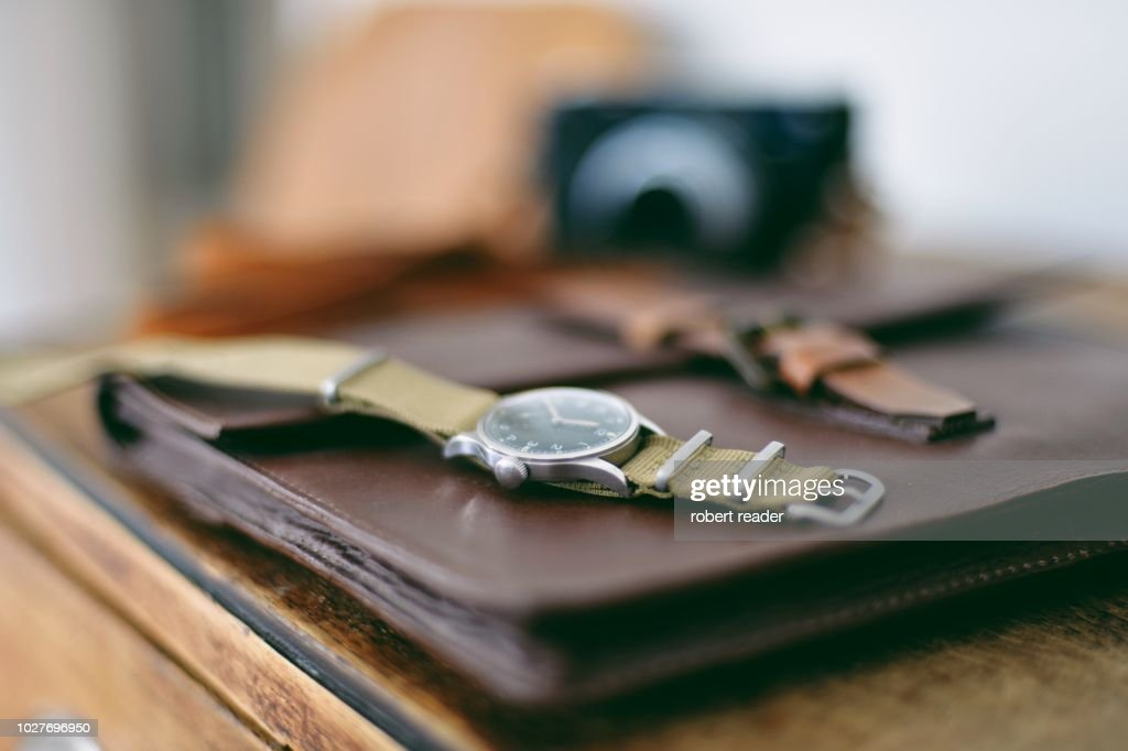 Military wristwatch on wooden cabinet : Stock Photo