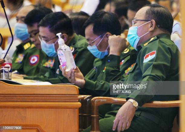 A militaryappointed member of parliament wearing a face mask amid fears about the spread of the COVID19 novel coronavirus looks at a bottle of...