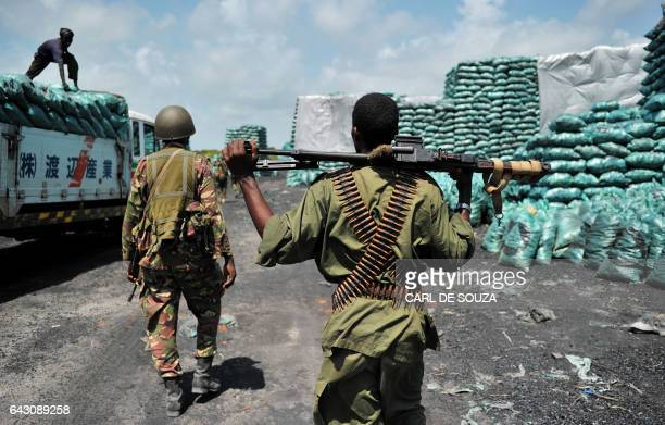 Militia allied with the Federal Government of Somalia and Kenyan Defence force soldiers walk through a charcoal loading area in Burgabo Southern...