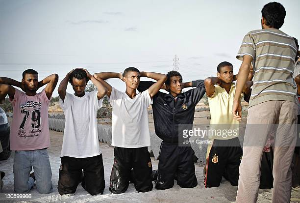 Militia fighters loyal to Gaddafi are captured and taunted by Misratan NTC fighters near Colonel Gaddafi's home city of Sirte on September 20 2011 in...