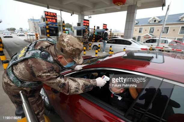 A militia member checks the body temperature of a driver on a vehicle at an expressway toll gate in Wuhan in central China's Hubei province Thursday...