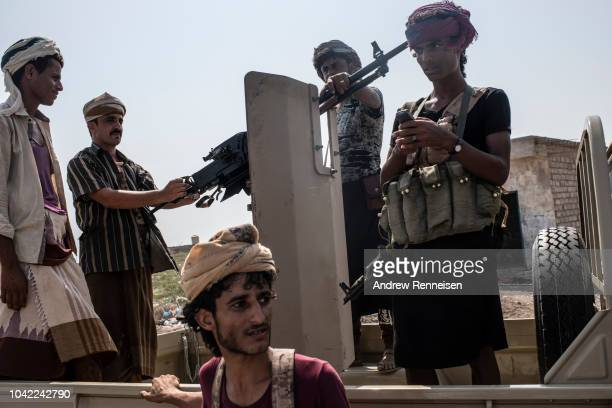 Militia members aligned with Yemen's Saudiled coalitionbacked government sit in the back of a truck prior to heading to the frontline of fighting on...