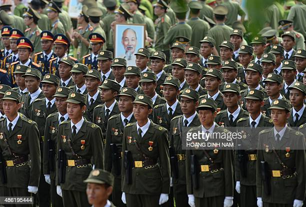 Militia soldiers stand as they listen to speeches prior to a parade in front of the mausoleum of late president Ho Chi Minh founder of today's...