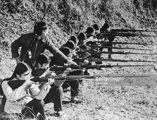 Militia woman teaching a group of young women how to handle rifles with bayonets during an exercise in the Yank Ku district of Shandong | Location...