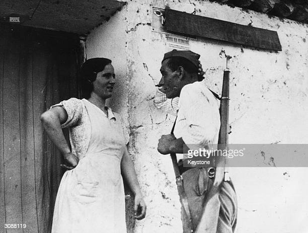 Militiaman chats with a woman in the doorway of her home in Extremadura or Estremadura in west central Spain, during the Spanish Civil War. The...