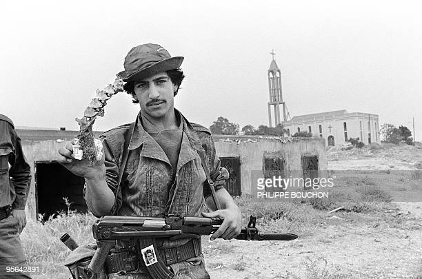 A militiaman from Amal movement displays 09 May 1985 in the Christian village of Jiyeh near Saida a vertebra column taken from mass burial pit In May...