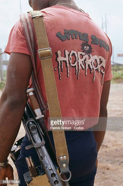 A militiaman from the National Patriotic Front of Liberia wears a shirt that says Little Shop of Horrors Responding to years of government corruption...