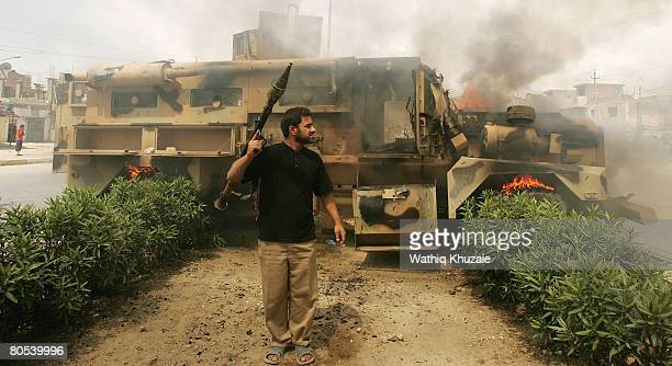 A militiaman loyal to the radical Shiite cleric Moqtda alSadr stands near a burning Iraqi Army vehicle during clashes between militiamen and Iraqi...