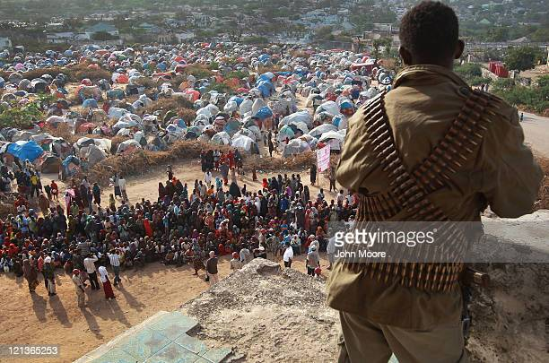 A militiaman watches as people wait for cooked food at camp for Somalis displaced by drought and famine on August 18 2011 in Mogadishu Somalia The...