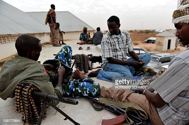 Militiamen chew on khat a narcotic leaf widely consumed in Somalia and which has stimulant qualities as they relax on the roof of a compound used by...