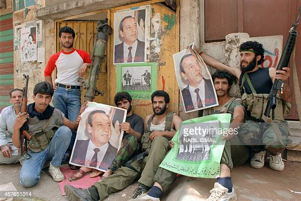 Militiamen from Amal the first political organization of Lebanon's Shi'ite Moslems holding portraits of their leader Nabih Berri relax 17 May 1988 in...