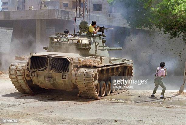 Militiamen from Amal the first political organization of Lebanon's Shi'ite Moslems fire from a tank 07 May 1988 in the Shi'ite southern suburb of...