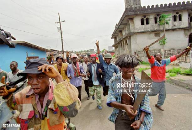 Militiamen of Charles Taylor's National Patriotic Front of Liberia jubilate 14 May 1996 in the streets of downtown Monrovia At least 15 fighters were...
