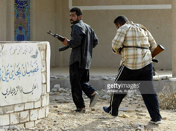 Militiamen of the Mehdi Army brandishing their rifles run past a grave with a sign giving direction to the grave of a man called Ghadban Ali in the...