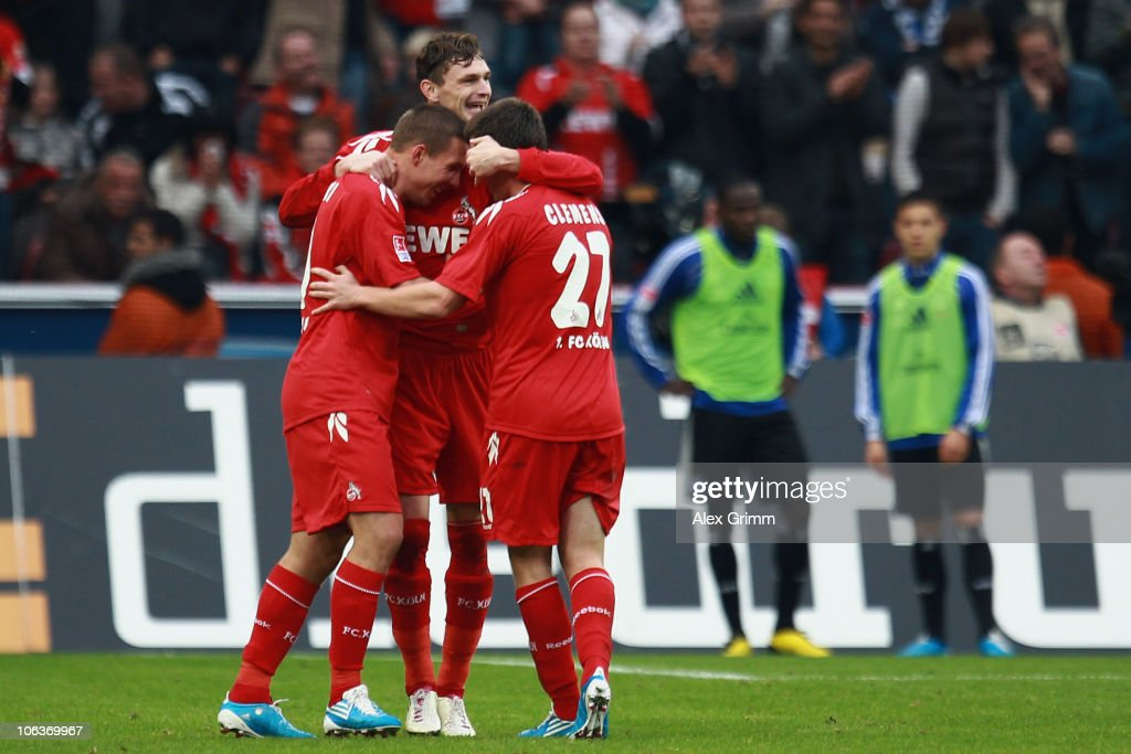 Milivoje Novakovic (C) of Koeln celebrates his team's third goal with team mates Lukas Podolski (L) and Christian Clemens (R) during the Bundesliga match between 1 FC Koeln and Hamburger SV at the RheinEnergieStadion on October 30, 2010 in Cologne, Germany.