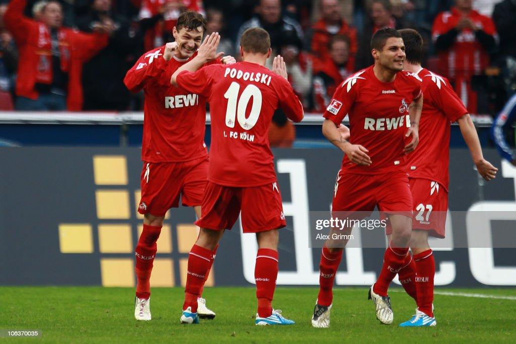 Milivoje Novakovic of Koeln celebrates his team's third goal with team mate Lukas Podolski (2L) during the Bundesliga match between 1 FC Koeln and Hamburger SV at the RheinEnergieStadion on October 30, 2010 in Cologne, Germany.