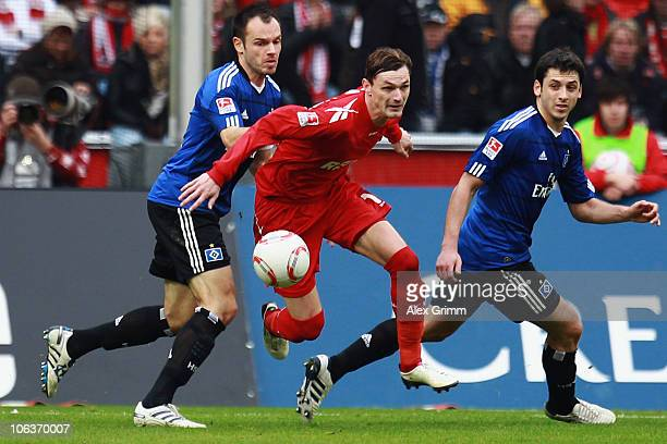 Milivoje Novakovic of Koeln is challenged by Heiko Westermann and Tomas Rincon of Hamburg during the Bundesliga match between 1 FC Koeln and...