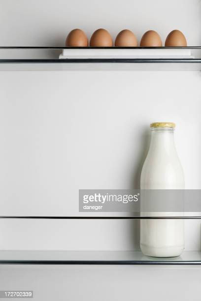 Milk and eggs inside an otherwise empty fridge