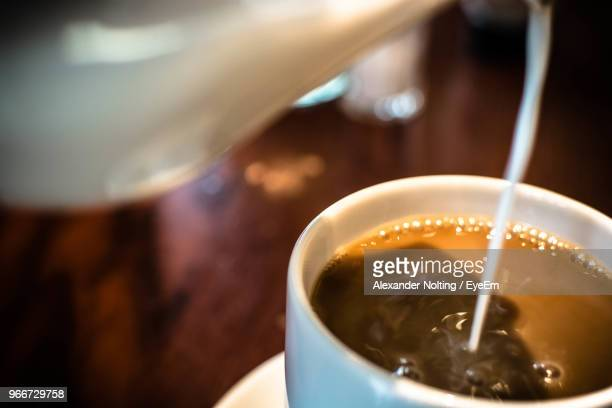 Milk Being Poured In Coffee