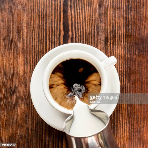 milk being poured into a cup of coffee. - milk pour stock photos and pictures