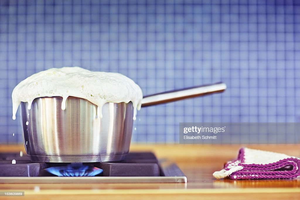 Milk boiling over in pan : Stock Photo