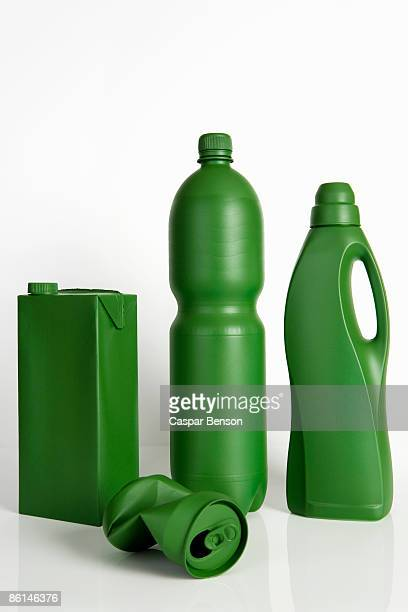 A milk carton, soda can, water bottle and laundry detergent bottle painted green