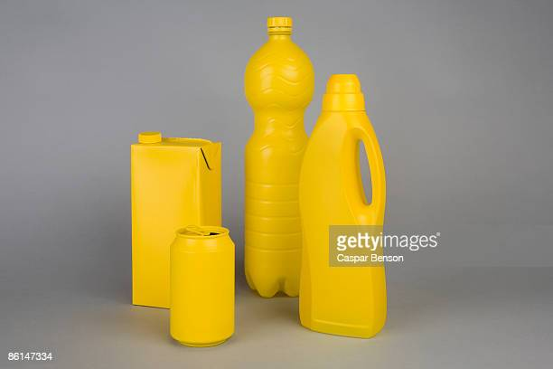 A milk carton, soda can, water bottle and laundry detergent bottle painted yellow